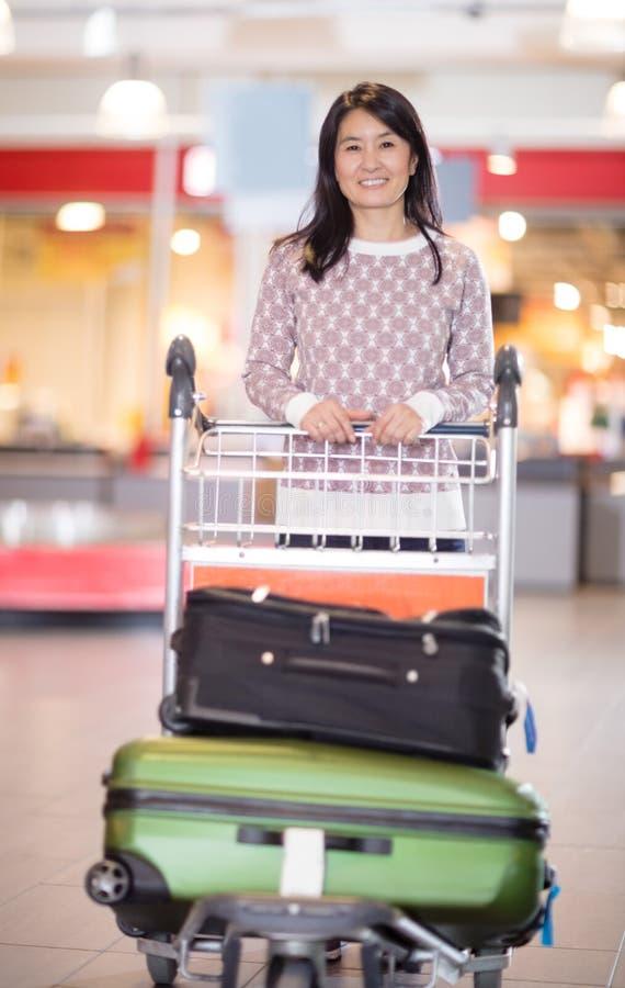 Ευτυχής μέση ενήλικη γυναίκα με τις αποσκευές στο κάρρο στον αερολιμένα στοκ εικόνες