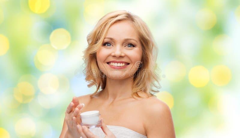 Ευτυχής μέση ηλικίας γυναίκα με το βάζο κρέμας στοκ εικόνα