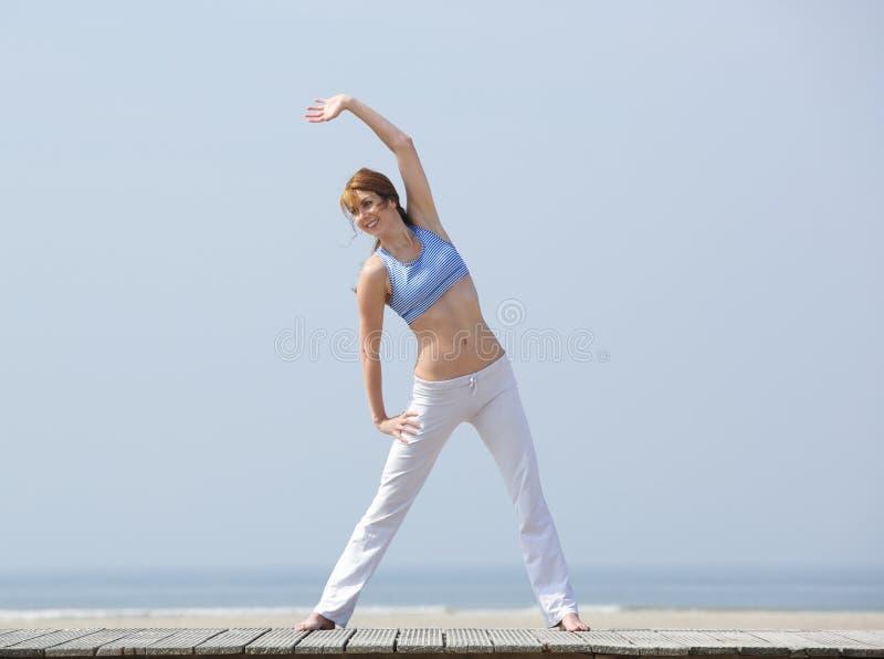 Ευτυχής μέση ηλικίας γυναίκα που ασκεί στην παραλία στοκ εικόνες με δικαίωμα ελεύθερης χρήσης