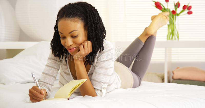 Ευτυχής μαύρη γυναίκα που γράφει στο περιοδικό στοκ φωτογραφίες με δικαίωμα ελεύθερης χρήσης