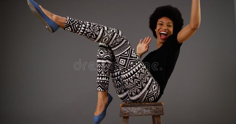 Ευτυχής μαύρη γυναίκα που χορεύει στην καρέκλα στοκ εικόνα με δικαίωμα ελεύθερης χρήσης
