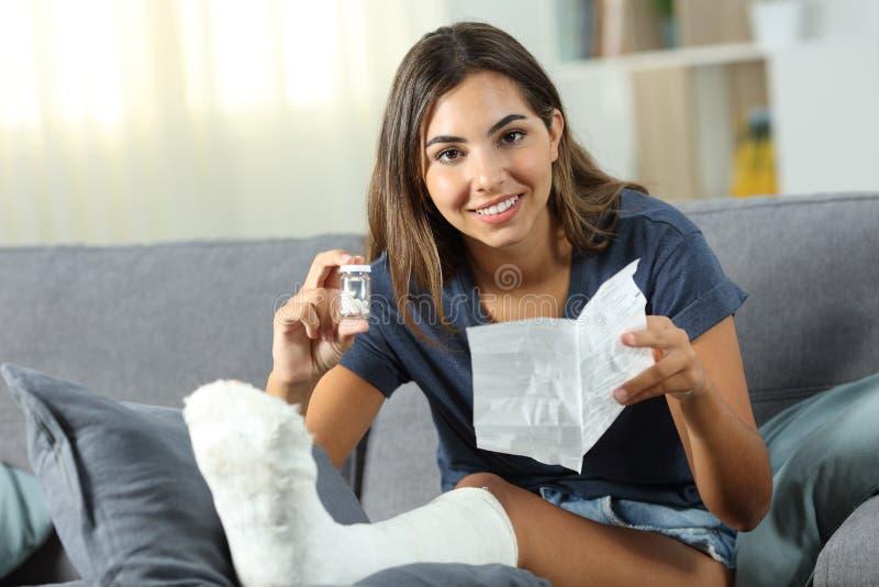 Ευτυχής με ειδικές ανάγκες γυναίκα που παρουσιάζει ένα μπουκάλι των χαπιών στοκ φωτογραφία