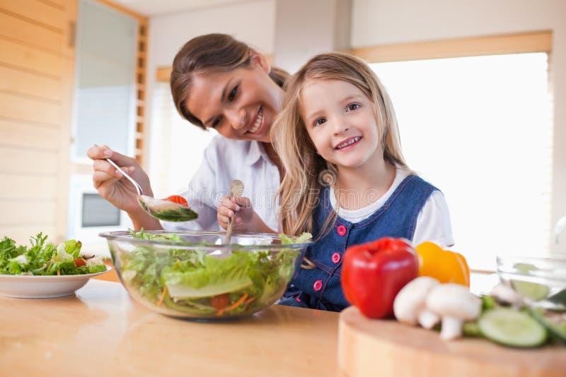 Ευτυχής μητέρα και η κόρη της που προετοιμάζουν μια σαλάτα στοκ φωτογραφία με δικαίωμα ελεύθερης χρήσης