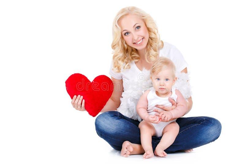 Ευτυχής μητέρα και το παιδί της που κρατούν μια κόκκινη καρδιά στοκ εικόνες