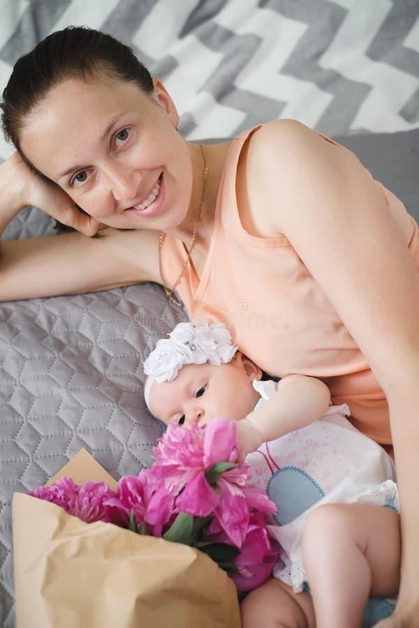 Ευτυχής μητέρα και χαριτωμένο μωρό στο κρεβάτι στοκ φωτογραφία
