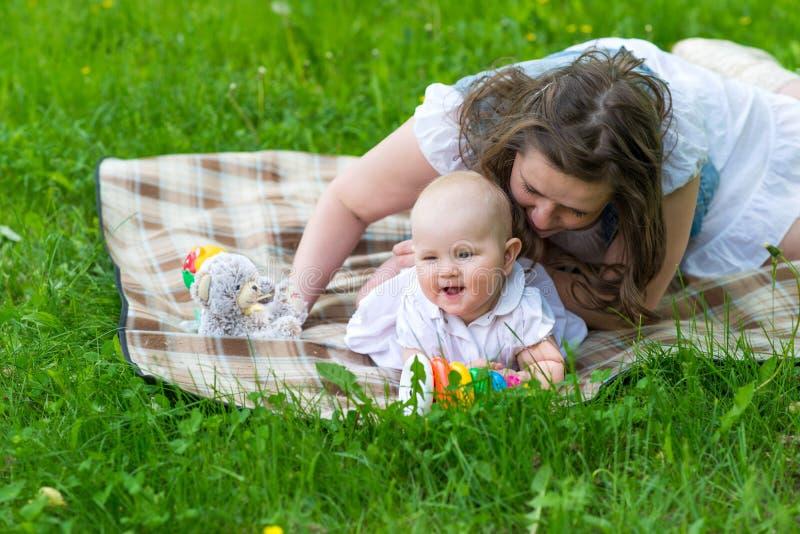 Ευτυχής μητέρα και χαριτωμένο παιχνίδι κοριτσάκι υπαίθριες στοκ εικόνες με δικαίωμα ελεύθερης χρήσης