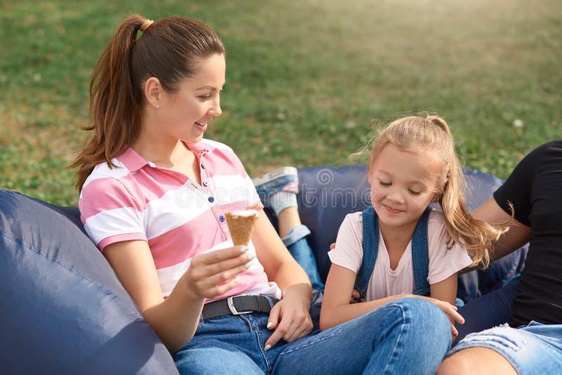 Ευτυχής μητέρα και doughter κατοχή της διασκέδασης και παίζοντας υπαίθρια, στέλνοντας το ελεύθερο χρόνο μαζί στη φύση, τρώγοντας  στοκ εικόνες