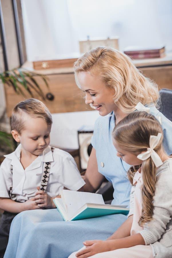 ευτυχής μητέρα με τα λατρευτά παιδάκια που διαβάζουν τη δεκαετία του '50 βιβλίων μαζί στο σπίτι στοκ φωτογραφία