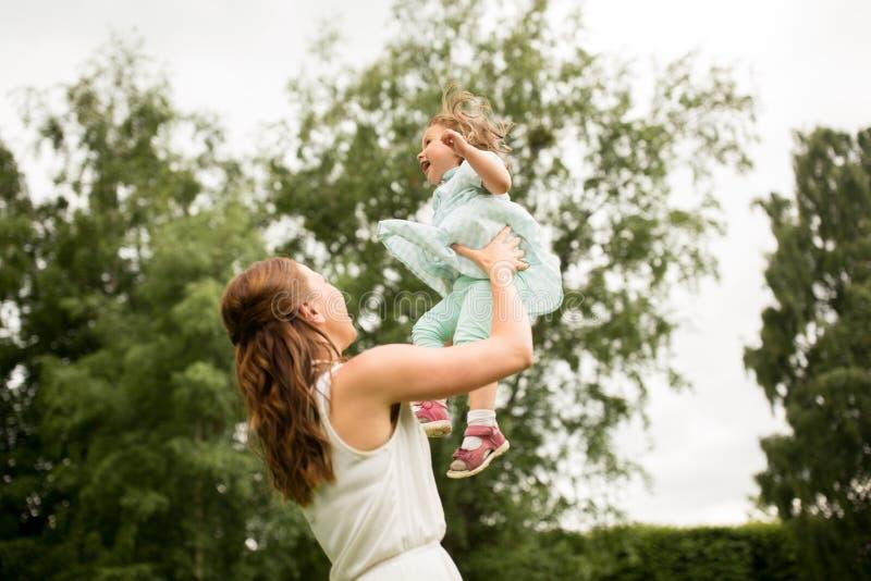 Ευτυχής μητέρα με την κόρη μωρών στο θερινό πάρκο στοκ εικόνα με δικαίωμα ελεύθερης χρήσης