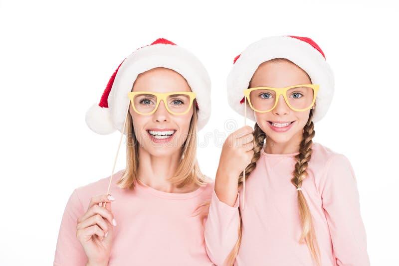 Ευτυχής μητέρα με την κόρη στα καπέλα santa και τα γυαλιά κομμάτων χαρτονιού στα Χριστούγεννα, στοκ φωτογραφία