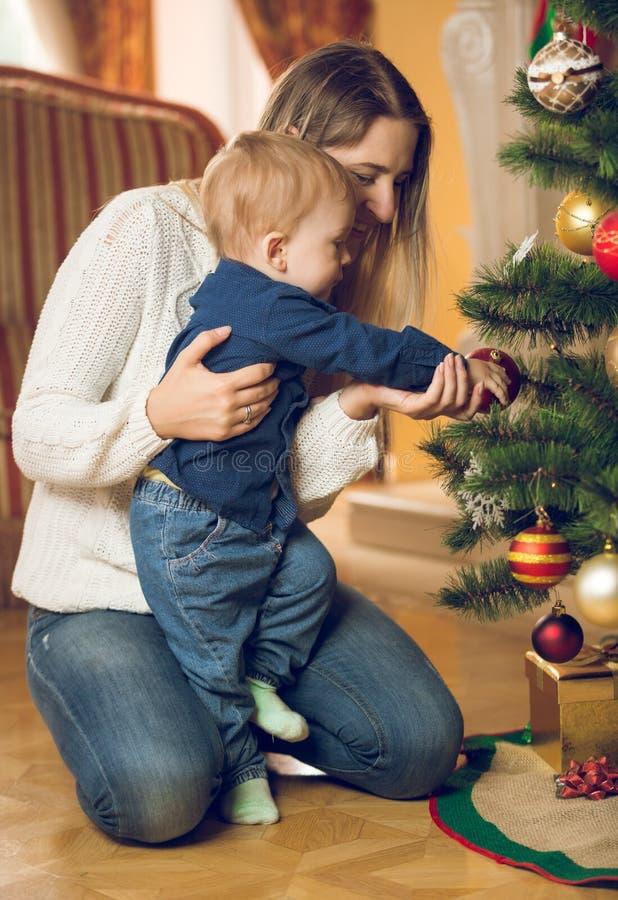 Ευτυχής μητέρα με το αγοράκι 10 μηνών της που διακοσμεί Christma στοκ φωτογραφία