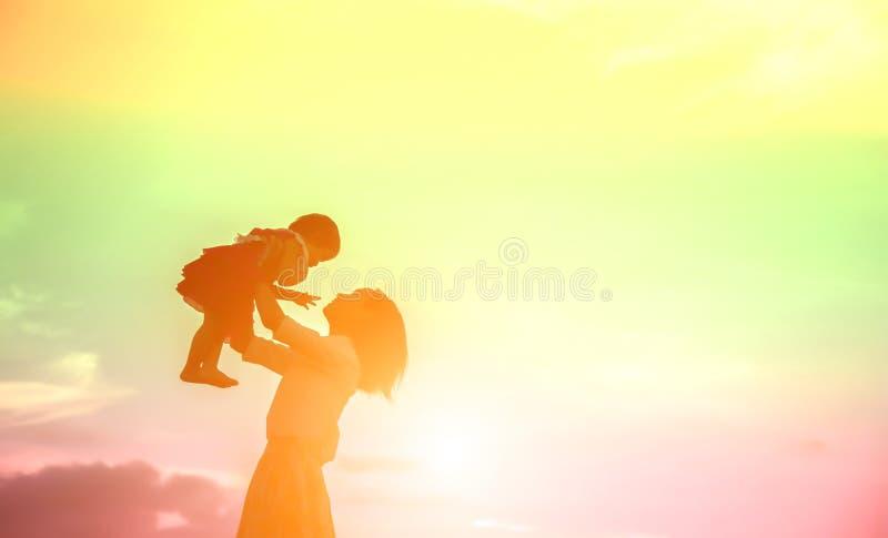 Ευτυχής μητέρα με το ηλιοβασίλεμα μωρών στοκ εικόνα
