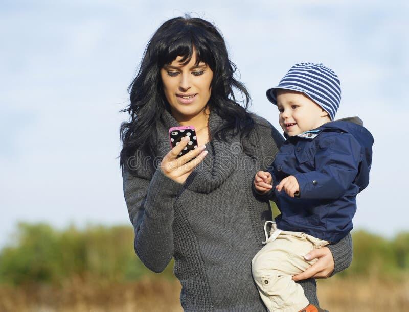 Ευτυχής μητέρα με το μικρό παιδί στο κινητό τηλέφωνο στοκ φωτογραφίες με δικαίωμα ελεύθερης χρήσης