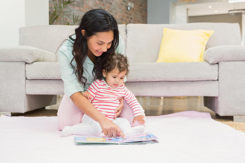 Ευτυχής μητέρα με το μωρό της που εξετάζει ένα βιβλίο στοκ εικόνες με δικαίωμα ελεύθερης χρήσης