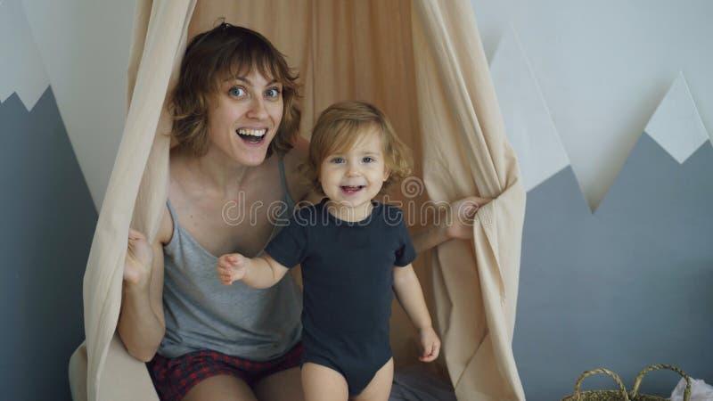 Ευτυχής μητέρα με το νέο χαριτωμένο παιχνίδι κορών και και δορά πίσω από την κουρτίνα στο σπίτι στοκ εικόνα