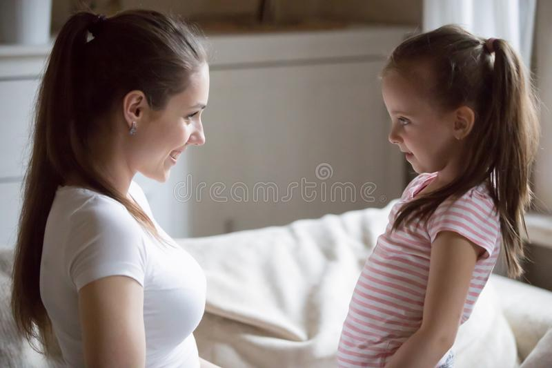 Ευτυχής μητέρα που εξετάζει τη χαμογελώντας κόρη που κρατά τα χέρια τη στοκ φωτογραφία