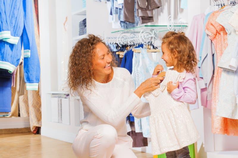 Ευτυχής μητέρα που δοκιμάζει το φόρεμα στην κόρη της στοκ φωτογραφία