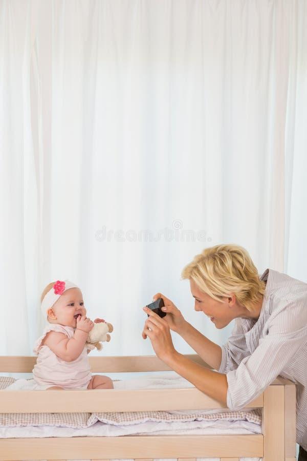 Ευτυχής μητέρα που παίρνει μια εικόνα του κοριτσάκι της στοκ εικόνες