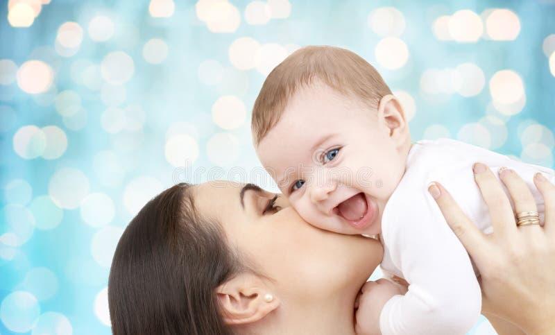 Ευτυχής μητέρα που φιλά το μωρό της πέρα από τα μπλε φω'τα στοκ φωτογραφίες με δικαίωμα ελεύθερης χρήσης