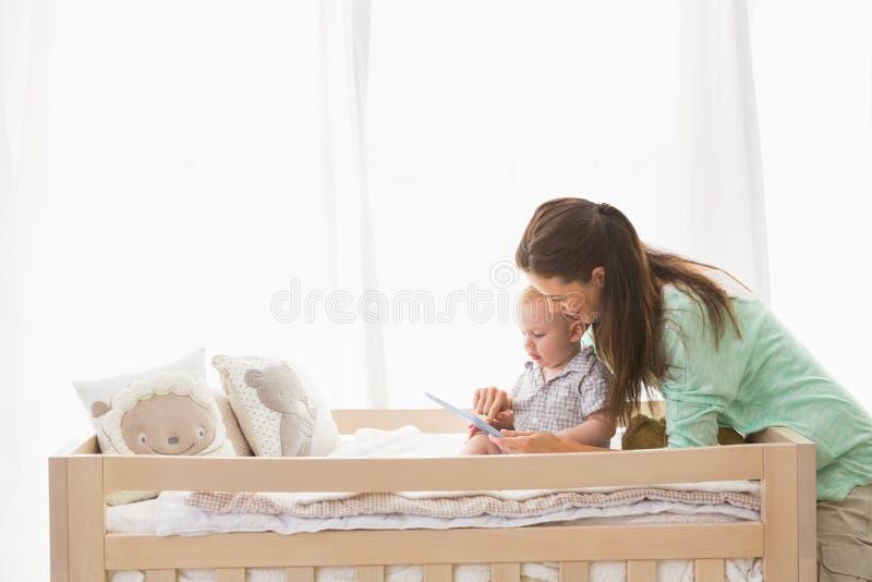 Ευτυχής μητέρα που χρησιμοποιεί την ταμπλέτα με το αγοράκι του στοκ φωτογραφία με δικαίωμα ελεύθερης χρήσης