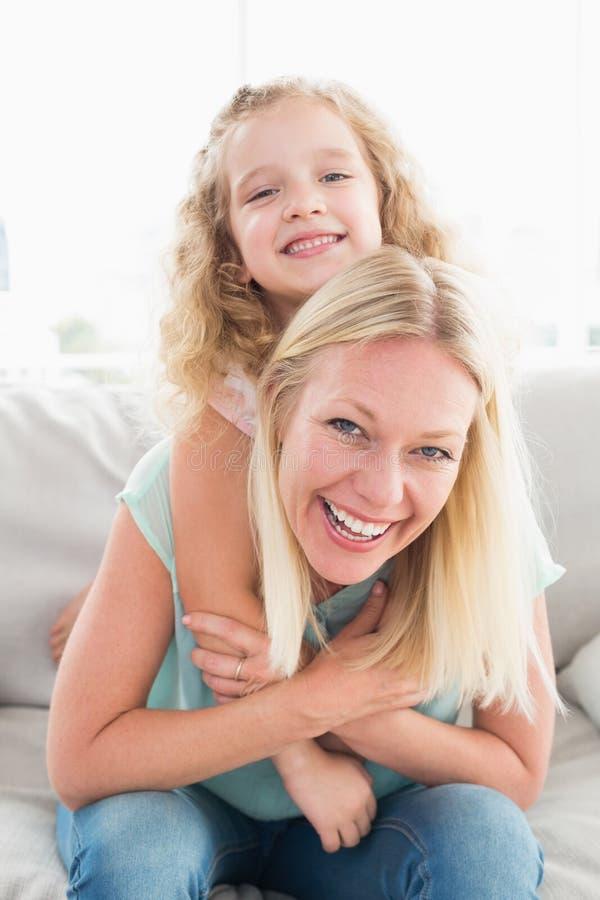 Ευτυχής μητέρα piggybacking η κόρη στον καναπέ στοκ εικόνες