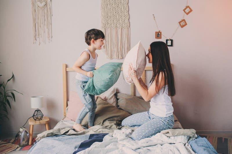 Ευτυχής μητέρων και παιδιών πάλη μαξιλαριών γιων παίζοντας στο κρεβάτι στα ξημερώματα στοκ εικόνα με δικαίωμα ελεύθερης χρήσης