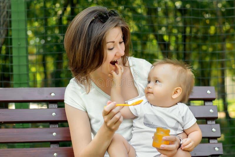 Ευτυχής μητρότητα: εύθυμο παιχνίδι νηπίων με τη συνεδρίαση μητέρων στα γόνατά της στο πάρκο Το Mom ταΐζει το παιδί με τον πουρέ σ στοκ φωτογραφίες με δικαίωμα ελεύθερης χρήσης