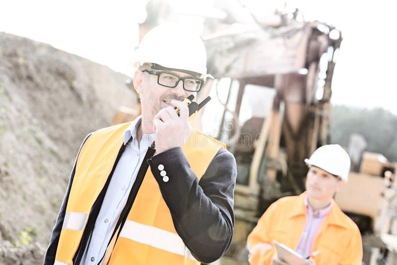 Ευτυχής μηχανικός που χρησιμοποιεί walkie-talkie στο εργοτάξιο οικοδομής με το συνάδελφο στο υπόβαθρο στοκ εικόνα με δικαίωμα ελεύθερης χρήσης