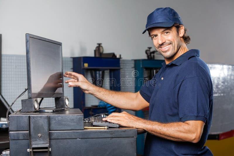 Ευτυχής μηχανικός χρησιμοποιώντας υπολογιστής στο κατάστημα επισκευής στοκ φωτογραφίες