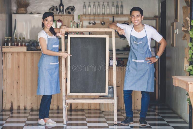 Ευτυχής μικρός ιδιοκτήτης επιχείρησης δύο έτοιμος να ανοίξει τον καφέ τους στοκ εικόνες με δικαίωμα ελεύθερης χρήσης