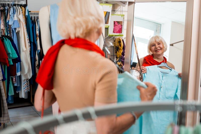 Ευτυχής μοντέρνη ηλικιωμένη γυναίκα μπροστά από τον καθρέφτη καταστημάτων αγορών στοκ φωτογραφίες με δικαίωμα ελεύθερης χρήσης