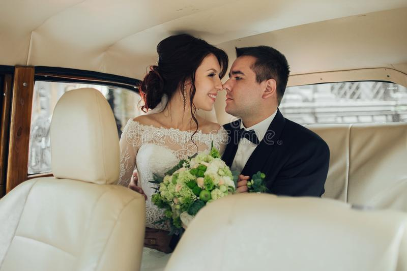 Ευτυχής μοντέρνος η τοποθέτηση ζευγών στο αναδρομικό αυτοκίνητο στοκ φωτογραφίες με δικαίωμα ελεύθερης χρήσης