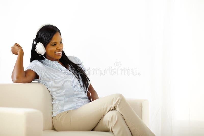 ευτυχής μουσική ακούσματος στις νεολαίες γυναικών στοκ φωτογραφία με δικαίωμα ελεύθερης χρήσης