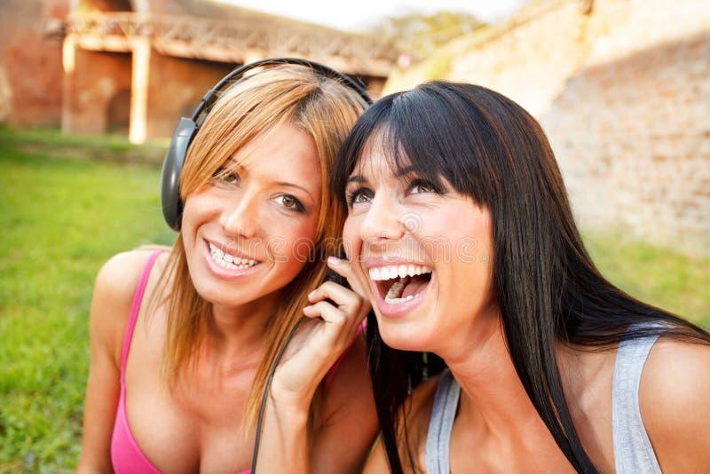 Ευτυχής μουσική ακούσματος φίλων κοριτσιών στοκ φωτογραφίες
