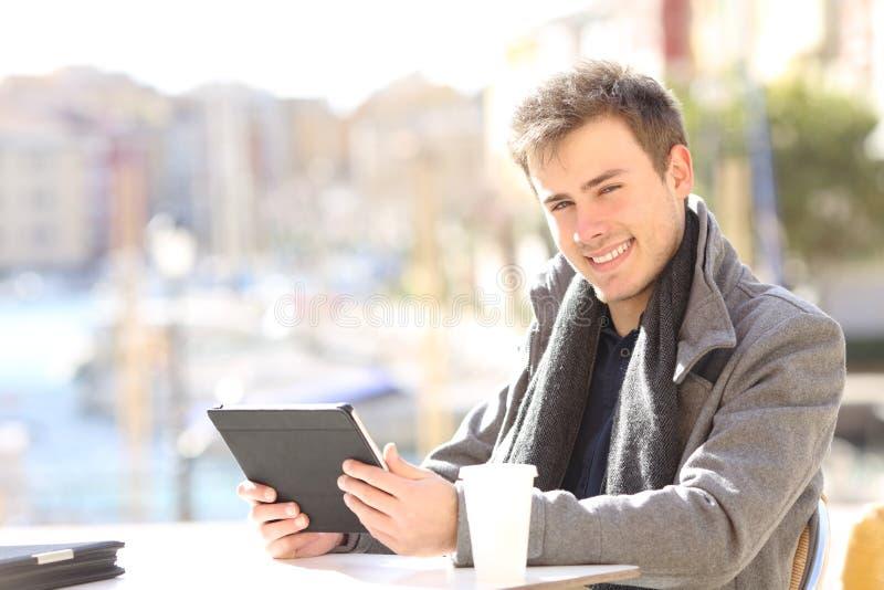 Ευτυχής μόνος - υιοθετημένος κρατώντας την ταμπλέτα εξετάζοντας σας στοκ εικόνα