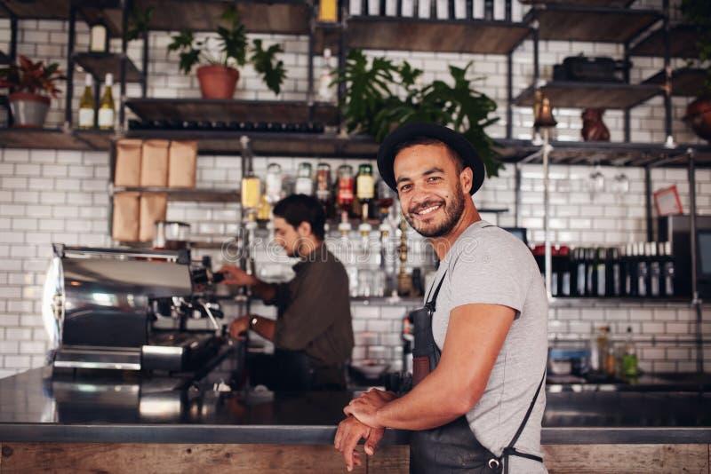 Ευτυχής νέα αρσενική στάση ιδιοκτητών καφετεριών στοκ εικόνες με δικαίωμα ελεύθερης χρήσης