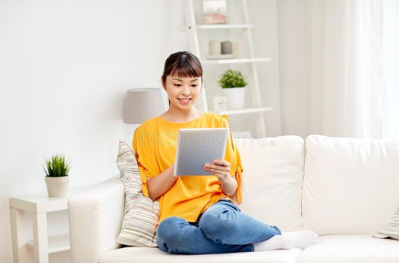 Ευτυχής νέα ασιατική γυναίκα με το PC ταμπλετών στο σπίτι στοκ εικόνες με δικαίωμα ελεύθερης χρήσης