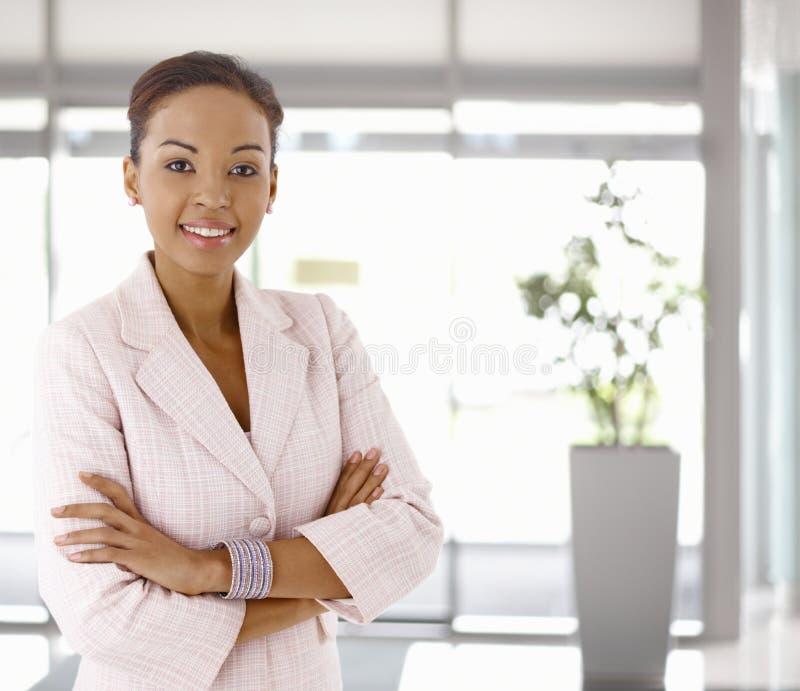 Ευτυχής νέα αφροαμερικανίδα γυναίκα στο λόμπι γραφείων στοκ φωτογραφία με δικαίωμα ελεύθερης χρήσης
