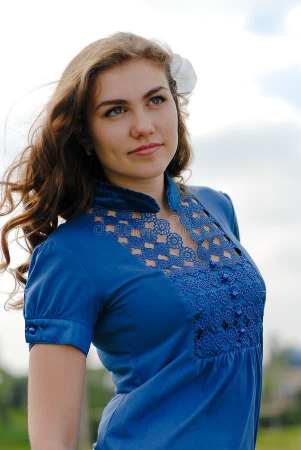 Ευτυχής νέα βέβαια γυναίκα στο μπλε χαμόγελο μπλουζών στοκ φωτογραφίες με δικαίωμα ελεύθερης χρήσης