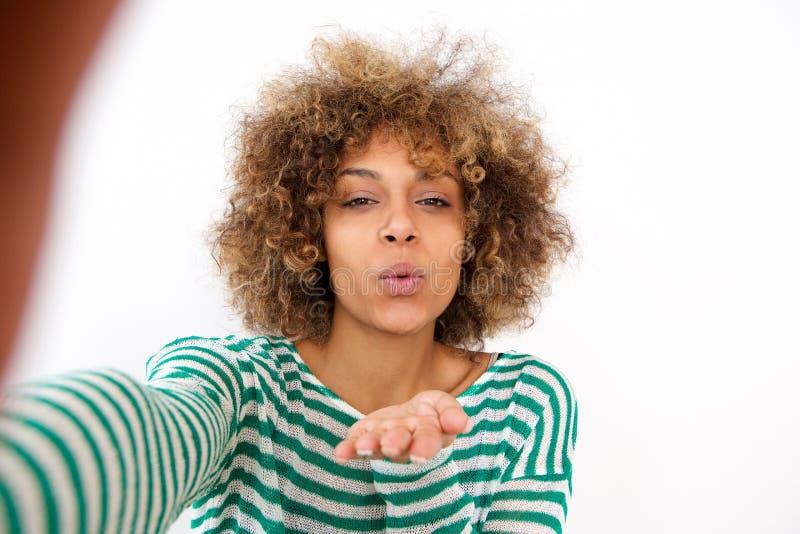 Ευτυχής νέα γυναίκα αφροαμερικάνων που παίρνει selfie και που φυσά ένα φιλί στοκ φωτογραφία