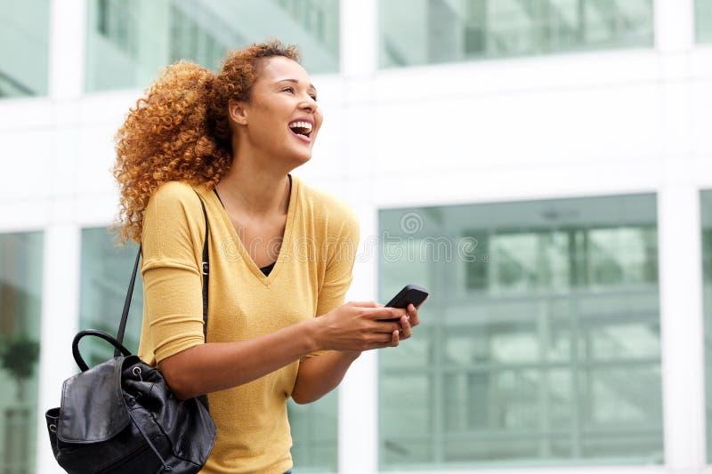 Ευτυχής νέα γυναίκα με στην πόλη με το κινητό τηλέφωνο στοκ εικόνες