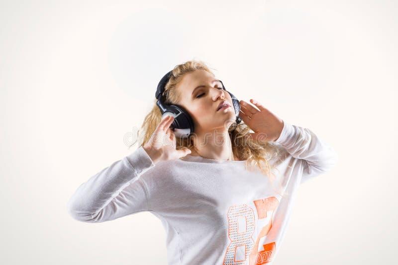 Ευτυχής νέα γυναίκα με τα ακουστικά που ακούει τη μουσική στοκ εικόνες
