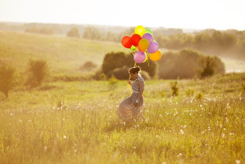 Ευτυχής νέα γυναίκα με τα μπαλόνια μεταξύ ενός τομέα στοκ φωτογραφίες με δικαίωμα ελεύθερης χρήσης