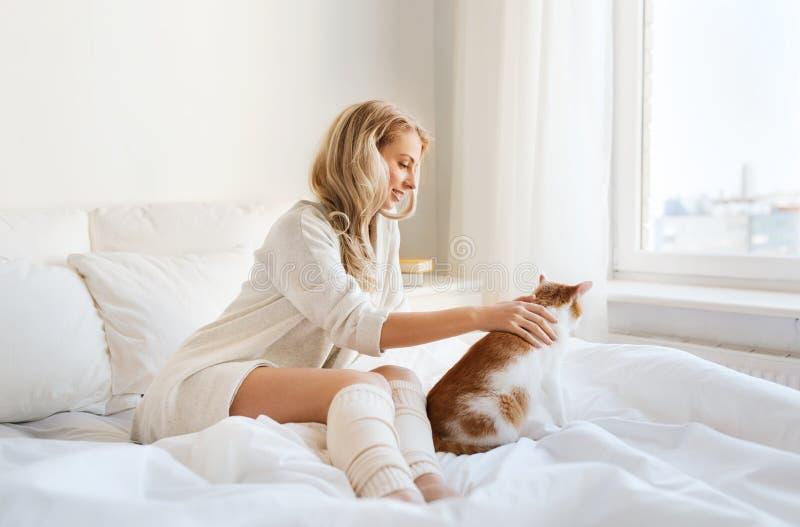 Ευτυχής νέα γυναίκα με τη γάτα στο κρεβάτι στο σπίτι στοκ φωτογραφίες