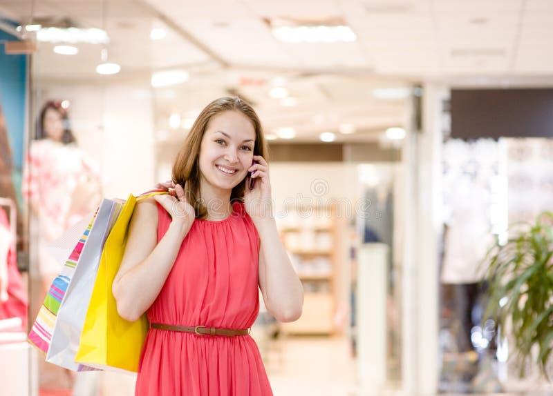 Ευτυχής νέα γυναίκα με τις τσάντες που μιλούν στο τηλέφωνο στοκ εικόνα με δικαίωμα ελεύθερης χρήσης