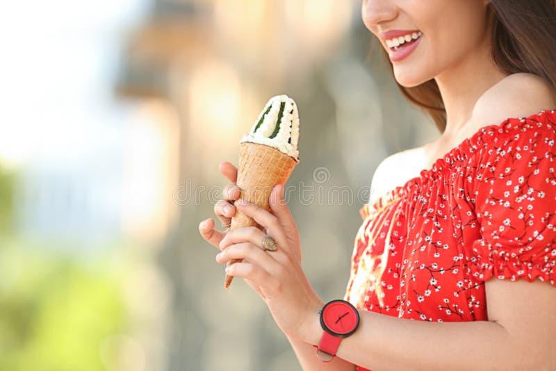Ευτυχής νέα γυναίκα με το εύγευστο παγωτό στον κώνο βαφλών υπαίθρια, κινηματογράφηση σε πρώτο πλάνο στοκ φωτογραφίες