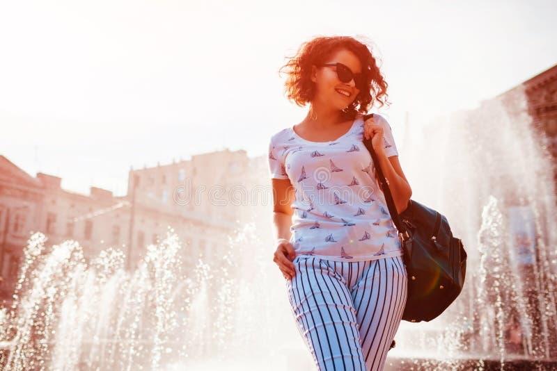 Ευτυχής νέα γυναίκα με το σακίδιο πλάτης που περπατά από την πηγή το καλοκαίρι Κατάψυξη κοριτσιών κολλεγίου μετά από τις κατηγορί στοκ φωτογραφία