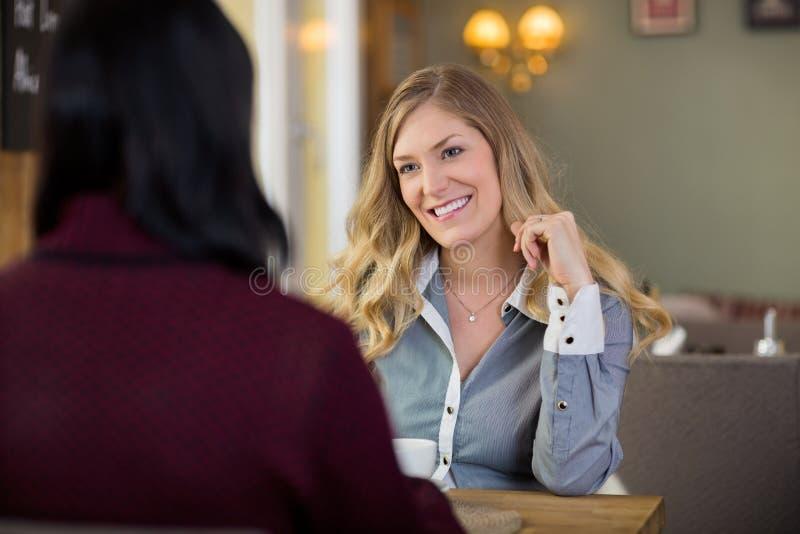 Ευτυχής νέα γυναίκα με το φίλο που έχει τον καφέ στοκ εικόνα