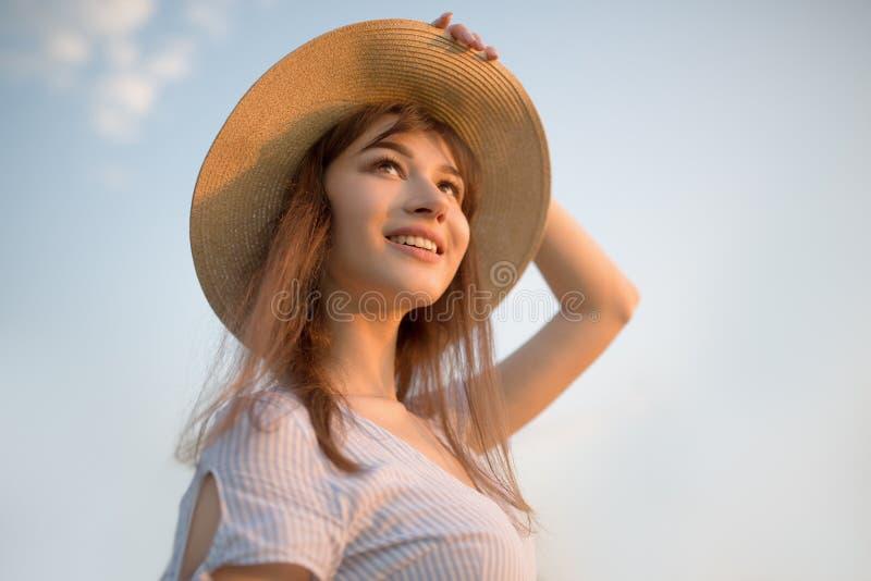 Ευτυχής νέα γυναίκα πέρα από το υπόβαθρο μπλε ουρανού Γυναίκα στο φόρεμα και το καπέλο στοκ εικόνες με δικαίωμα ελεύθερης χρήσης