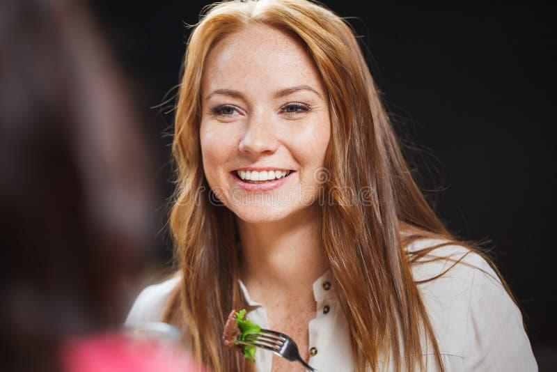 Ευτυχής νέα γυναίκα που έχει το γεύμα στο εστιατόριο στοκ εικόνες με δικαίωμα ελεύθερης χρήσης